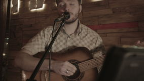 Ο μουσικός τραγουδά πριν από το ακροατήριο που τιτιβίζει στο κείμενο απόθεμα βίντεο
