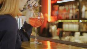 Ο μπάρμαν δίνει το κοκτέιλ σε μια γυναίκα στο μπαρ απόθεμα βίντεο