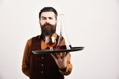 Ο μπάρμαν με το σοβαρό πρόσωπο εξυπηρετεί σκωτσέζικο ή το κονιάκ στοκ φωτογραφία με δικαίωμα ελεύθερης χρήσης