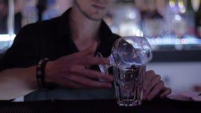 Ο μπάρμαν με δύο ποτήρια κάνει ένα κοκτέιλ στο νυχτερινό κέντρο διασκέδασης φιλμ μικρού μήκους
