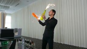 Ο μπάρμαν που κάνει ταχυδακτυλουργίες και που κάνει κλίσεων κινείται στο φραγμό με τα μπουκάλια και τα πυροτεχνήματα φιλμ μικρού μήκους