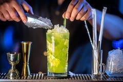Ο μπάρμαν προετοιμάζει ένα φρέσκο, κρύο κοκτέιλ στο μετρητή φραγμών Ποτό αγγουριών με το οινόπνευμα και τον ασβέστη Απίστευτο μίγ Στοκ φωτογραφία με δικαίωμα ελεύθερης χρήσης