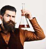 Ο μπάρμαν στο εκλεκτής ποιότητας γιλέκο κρατά σκωτσέζικος ή κονιάκ στοκ εικόνα