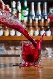 Ο μπάρμαν στο φραγμό χύνει ένα οινοπνευματώδες κοκτέιλ σε ένα ποτήρι με ένα ισχυρό ρεύμα, μη φοβισμένο να ανατρέψει στον πίνακα στοκ εικόνες
