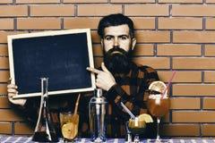Ο μπάρμαν, bartender ή hipster κρατά τη διαφήμιση φραγμών Έννοια επιλογών φραγμών Ο μπάρμαν με τη γενειάδα και το σοβαρό πρόσωπο  στοκ εικόνες
