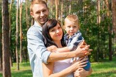 Ο μπαμπάς αγκαλιάζει mom που κρατά το παιδί στα όπλα της Ευτυχής οικογένεια - Mom Στοκ φωτογραφία με δικαίωμα ελεύθερης χρήσης