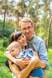 Ο μπαμπάς αγκαλιάζει mom που κρατά το παιδί στα όπλα της Ευτυχής οικογένεια - Mom Στοκ Εικόνες
