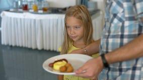 Ο μπαμπάς βάζει τα πρόχειρα φαγητά στο πιάτο της κόρης του Στοκ εικόνα με δικαίωμα ελεύθερης χρήσης
