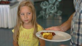 Ο μπαμπάς βάζει τα πρόχειρα φαγητά στο πιάτο της κόρης του Στοκ Εικόνες