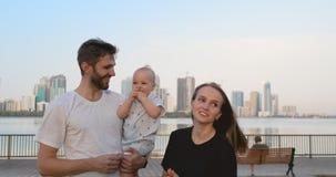Ο μπαμπάς γονέων πόλεων mom ανατρέφει το γιο της που στέκεται στην προκυμαία στο υπόβαθρο της πόλης απόθεμα βίντεο