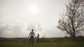 Ο μπαμπάς διδάσκει την κόρη πώς να οδηγήσει το ποδήλατο στο λιβάδι στο χρόνο ηλιοβασιλέματος Ο ευτυχής πατέρας χαίρεται ότι η κόρ απόθεμα βίντεο