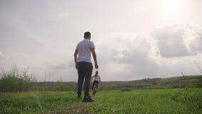 Ο μπαμπάς διδάσκει την κόρη πώς να οδηγήσει το ποδήλατο στο λιβάδι στο χρόνο ηλιοβασιλέματος Ο ευτυχής πατέρας χαίρεται ότι η κόρ φιλμ μικρού μήκους