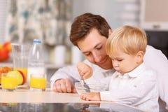 Ο μπαμπάς ενθαρρύνει το γιο του για να τελειώσει δημητριακά στοκ εικόνα με δικαίωμα ελεύθερης χρήσης