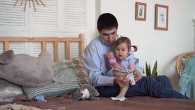 Ο μπαμπάς κάθεται στο κρεβάτι του και βάζει στις κάλτσες του με τη μικρή κόρη του Ο μπαμπάς κρατά την κόρη στα όπλα του φιλμ μικρού μήκους