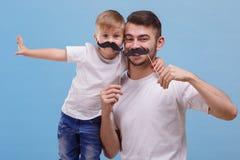 Ο μπαμπάς και ο γιος του στέκονται δίπλα-δίπλα σε ένα μπλε υπόβαθρο Μπροστινή όψη Στοκ Εικόνες