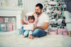 Ο μπαμπάς και η κόρη κάθονται και ανοίγουν ένα χριστουγεννιάτικο δώρο κοντά στο χριστουγεννιάτικο δέντρο καλή χρονιά Στοκ φωτογραφία με δικαίωμα ελεύθερης χρήσης
