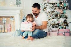 Ο μπαμπάς και η κόρη κάθονται και ανοίγουν ένα χριστουγεννιάτικο δώρο κοντά στο χριστουγεννιάτικο δέντρο καλή χρονιά Στοκ Φωτογραφίες