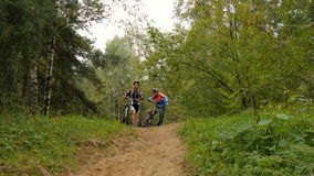 Ο μπαμπάς και ο γιος πηγαίνουν για μια κίνηση στα ξύλα στα ποδήλατα Γιορτάστε τη νίκη απόθεμα βίντεο