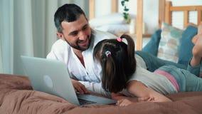 Ο μπαμπάς και το χαριτωμένο παιδί χρησιμοποιούν το lap-top στο κρεβάτι, παιχνίδι online παιχνιδιών, σε αργή κίνηση απόθεμα βίντεο
