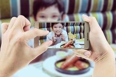 Ο μπαμπάς παίρνει την κινητή φωτογραφία του ασιατικού αγοριού που τρώει τις τηγανιτές πατάτες στοκ εικόνα με δικαίωμα ελεύθερης χρήσης