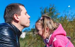 Ο μπαμπάς προσπαθεί να φιλήσει ένα κορίτσι Γελά Στο πάρκο στο ρόδινο παλτό Στοκ φωτογραφία με δικαίωμα ελεύθερης χρήσης