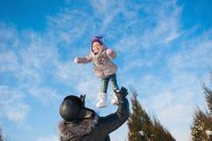Ο μπαμπάς ρίχνει επάνω στην κόρη μωρών το χειμώνα ενάντια στο μπλε ουρανό, τρόπος ζωής, χειμερινές διακοπές στοκ εικόνα με δικαίωμα ελεύθερης χρήσης