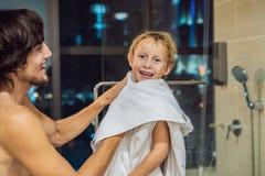 Ο μπαμπάς σκουπίζει το γιο του με μια πετσέτα μετά από ένα ντους στο BEF βραδιού στοκ εικόνα