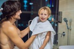 Ο μπαμπάς σκουπίζει το γιο του με μια πετσέτα μετά από ένα ντους στο BEF βραδιού στοκ εικόνες