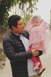 Ο μπαμπάς φαίνεται η κόρη της με το ευτυχές χαμόγελο όταν το παιδί του που φορά ένα vell στοκ φωτογραφία