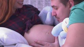 Ο μπαμπάς φιλά και χαϊδεύει την κοιλιά της συζύγου του που παίζει με τα μαλακά παιχνίδια Έννοια μητρότητας Εγκυμοσύνη οικογένεια  φιλμ μικρού μήκους