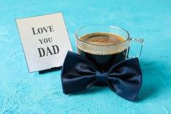 Ο μπλε δεσμός τόξων, το φλιτζάνι του καφέ και η επιγραφή σας αγαπούν DAD στο υπόβαθρο χρώματος στοκ φωτογραφία με δικαίωμα ελεύθερης χρήσης