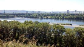 Ο μπλε ουρανός και ο μεγάλος ποταμός κοντά στην πόλη στο εργοστάσιο μανικών στοκ φωτογραφίες