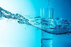 Ο μπλε παφλασμός νερού χύνει σε ένα γυαλί σε ένα όμορφο μπλε υπόβαθρο κυμάτων θάλασσας στοκ εικόνες