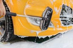Ο μπροστινός προφυλακτήρας και τα φω'τα του κίτρινου αυτοκινήτου που πλένεται σε μόνο εξυπηρετούν carwash, βούρτσα που κινείται σ στοκ εικόνες με δικαίωμα ελεύθερης χρήσης