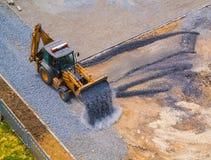 Ο μπροστινός φορτωτής έχυσε το αμμοχάλικο από την κουτάλα στο εργοτάξιο οικοδομής του σχολικού σταδίου στοκ εικόνες