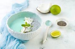 Ο μπλε καταφερτζής spirulina Vegan και το κύπελλο πουτίγκας chia που ολοκληρώνεται με την καρύδα ξεφλουδίζουν και την απόλαυση ασ Στοκ φωτογραφία με δικαίωμα ελεύθερης χρήσης