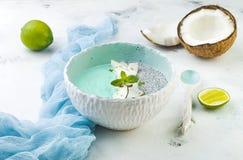 Ο μπλε καταφερτζής spirulina Vegan και το κύπελλο πουτίγκας chia που ολοκληρώνεται με την καρύδα ξεφλουδίζουν και την απόλαυση ασ Στοκ Φωτογραφίες