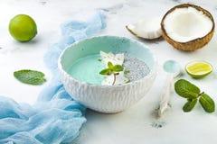 Ο μπλε καταφερτζής spirulina Vegan και το κύπελλο πουτίγκας chia που ολοκληρώνεται με την καρύδα ξεφλουδίζουν και την απόλαυση ασ Στοκ Εικόνα
