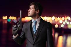 Ο μυστικός πράκτορας ή ο δολοφόνος κρατά το πυροβόλο όπλο με τον ησυχαστήρα διαθέσιμο τη νύχτα στοκ εικόνες