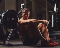 Ο μυϊκός αθλητής γυμνοστήθων κάθεται σε ένα πάτωμα που στηρίζεται μετά από ένα σκληρό workout στη γυμναστική Στοκ Εικόνες
