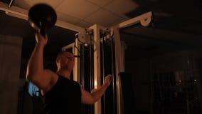 Ο μυϊκός αθλητής ανυψώνει τα βάρη στη γυμναστική απόθεμα βίντεο