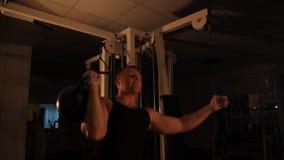 Ο μυϊκός αθλητής ανυψώνει τα βάρη στη γυμναστική φιλμ μικρού μήκους