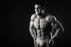 Ο μυϊκός αθλητής καταδεικνύει τους μυς του κάτω από το φορτίο σε ένα σκοτεινό υπόβαθρο Στοκ εικόνα με δικαίωμα ελεύθερης χρήσης
