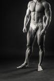 Ο μυϊκός αθλητής καταδεικνύει τους μυς του κάτω από το φορτίο σε ένα σκοτεινό υπόβαθρο Στοκ φωτογραφία με δικαίωμα ελεύθερης χρήσης