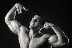 Ο μυϊκός αθλητής καταδεικνύει τους μυς του κάτω από το φορτίο σε ένα σκοτεινό υπόβαθρο Στοκ φωτογραφίες με δικαίωμα ελεύθερης χρήσης
