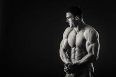 Ο μυϊκός αθλητής καταδεικνύει τους μυς του κάτω από το φορτίο σε ένα σκοτεινό υπόβαθρο Στοκ Φωτογραφία
