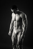 Ο μυϊκός αθλητής καταδεικνύει τους μυς του κάτω από το φορτίο σε ένα σκοτεινό υπόβαθρο Στοκ εικόνες με δικαίωμα ελεύθερης χρήσης