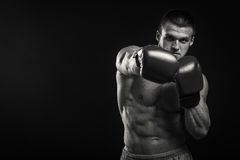 Ο μυϊκός αθλητής καταδεικνύει τους μυς του κάτω από το φορτίο σε ένα σκοτεινό υπόβαθρο Στοκ Εικόνες