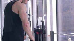 Ο μυϊκός ισχυρός αθλητής εκτελεί μια άσκηση για την κατάρτιση οικοδόμησης μυών στον προσομοιωτή έλξης εργαζόμενος στο σώμα απόθεμα βίντεο