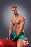 Ο μυϊκός μαχητής προετοιμάζεται για την άσκηση μερικών λακτισμάτων με Punching την τσάντα Στοκ Εικόνες